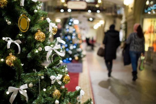 En julgran i ett centrum med två kvinnor som har handlat julklappar