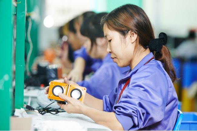 Kinesisk kvinna sitter och arbetar i en fabrik med linjeproduktion