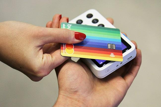 Två händer där en hand håller i en trådlös kortmaskin och en hand håller i det regnbågsfärgade betalkortet bunq
