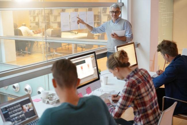 Lärare står i klassrum och lär ut ekonomi till elever som sitter bakom sina datorer och gör anteckningar.