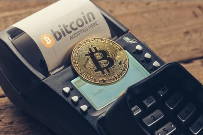 Ett bitcoinmynt som ligger på en betalkortsmaskin