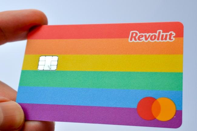 Tumme och pekfinger som håller i det nya regnbågsfärgade kreditkortet Revolut