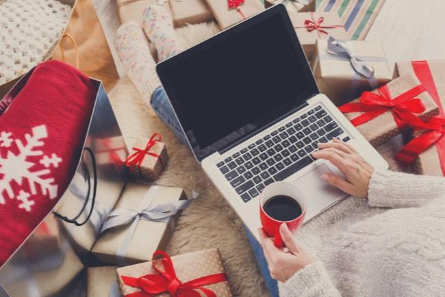 Kvinna som sitter med laptop i knät, kaffekopp i handen och julklappar runt omkring sig och handlar julklappar online.