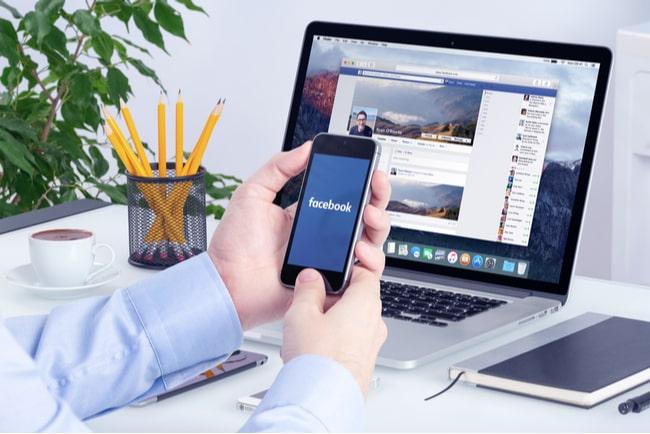 Man sitter vid skrivbord, håller i mobil och öppnar facebookappen. Framför sig har han en laptop