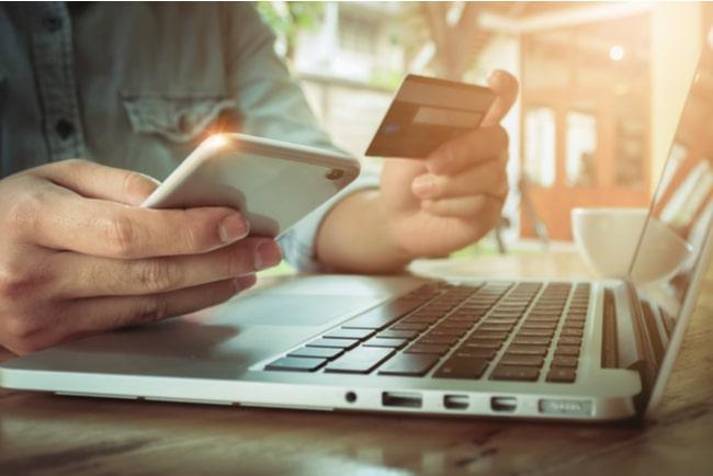 person som sitter vid en dator och håller i en telefon och ett kreditkort