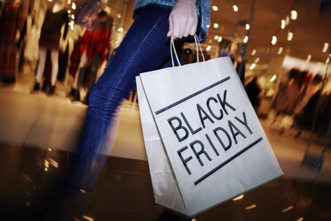 kvinna i shoppingcenter håller papperskasse med texten Black Friday på