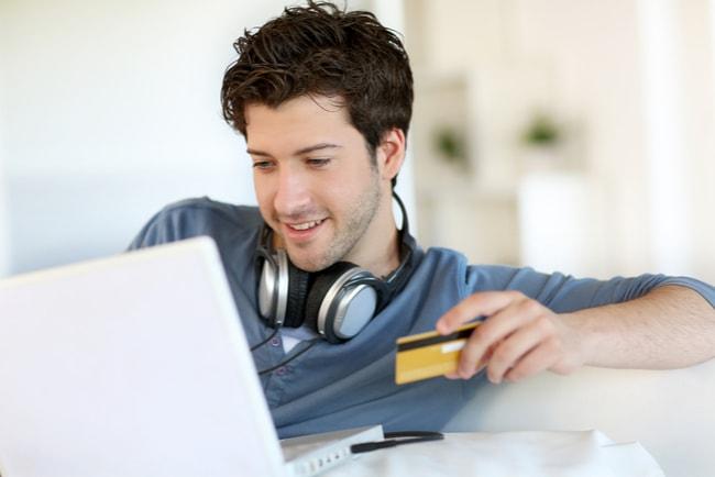 Ung man med en laptop i knät och ett kreditkort i handen