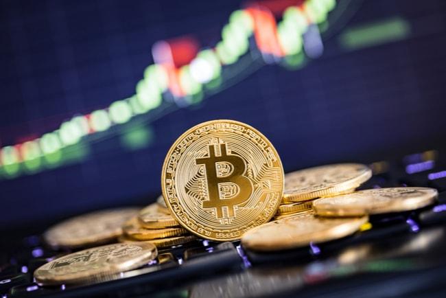 Flera bitcoin och ett diagram i bakgrunden.