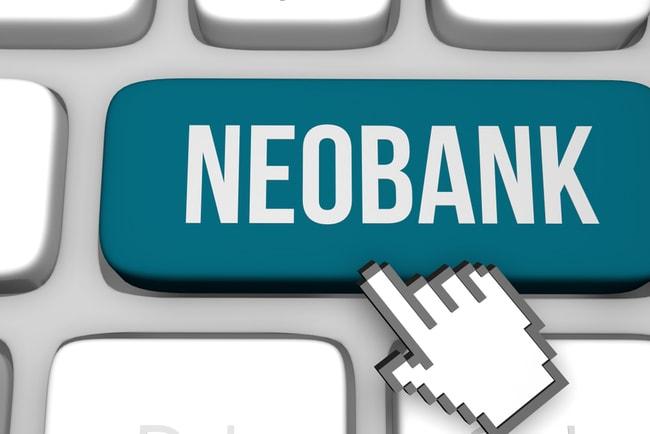 Del av tangentbord med en miniatyrhand som pekar på en tangent som det står Neobank på.