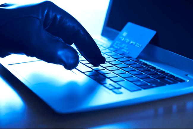 Cyberbrottslings hand med handske, bärbar dator och ett stulet kreditkort