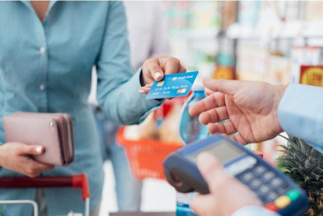 Kvinna sträcker fram betalkort till kassör i butik