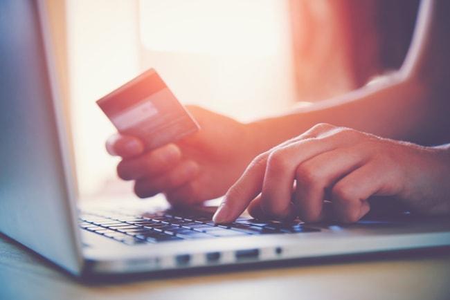 Kvinna sitter framför laptop och knappar på tangentbordet med vänster hand och håller i ett kreditkort med höger hand.