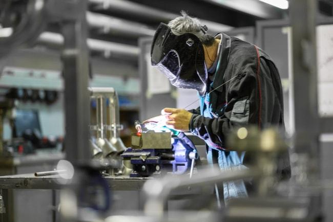 Industriarbetare med skyddsmask står och svetsar