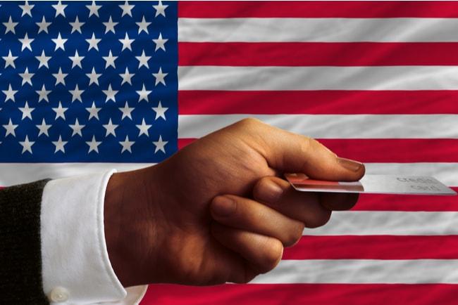 Man håller fram ett kreditkort framför den amerikanske flaggan som syns i bakgrunden.