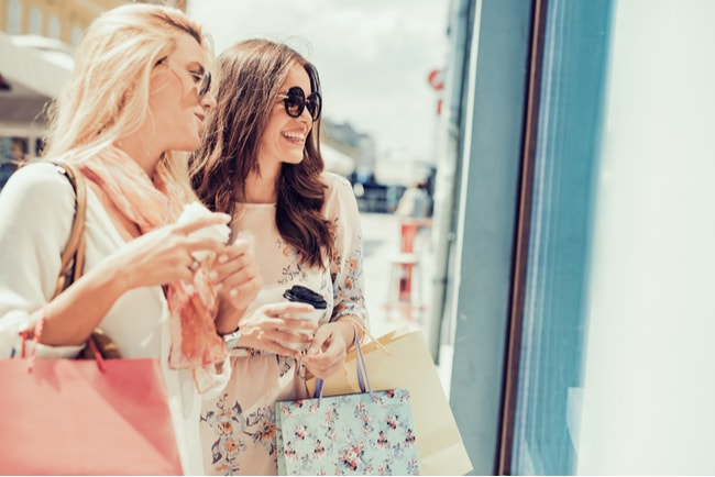 Två unga kvinnor håller i shoppingbagar och take away kaffe och tittar i skyltfönster