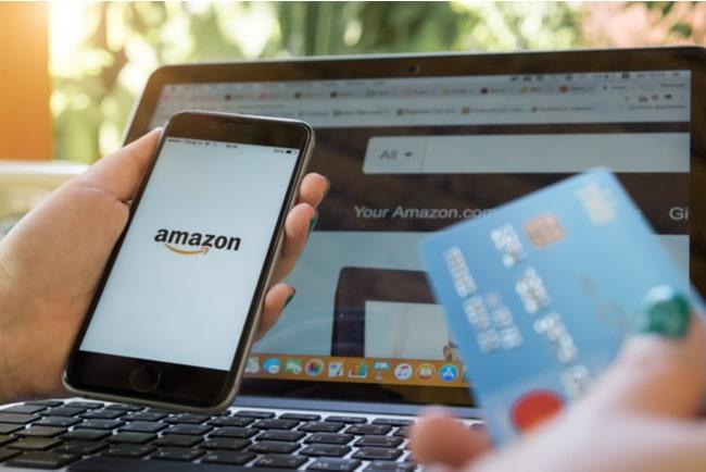 hand håller mobil och betalkort med dator framför med dator framför