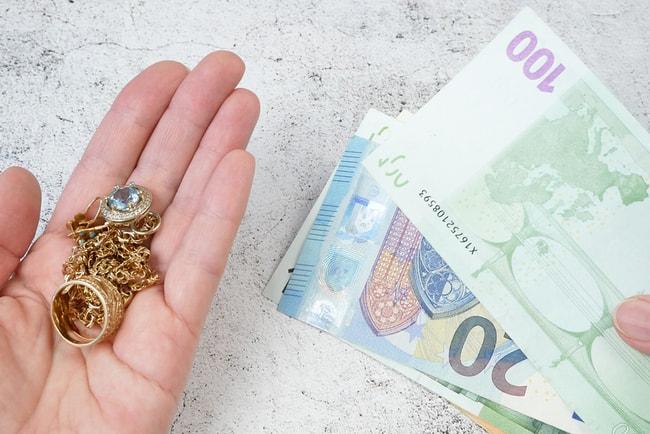 Hand som håller i olika smycken som pantsätts och får pengar