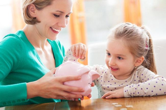 en mor håller i spargris medan liten dotter stoppar i mynt