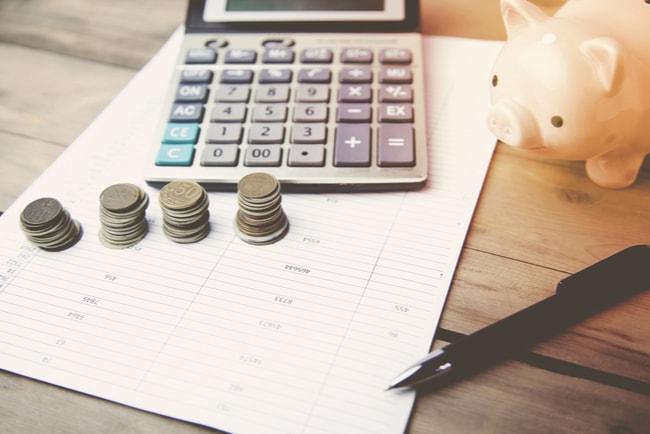 En spargris, miniräknare och tre högar med mynt ståendes på ett bord