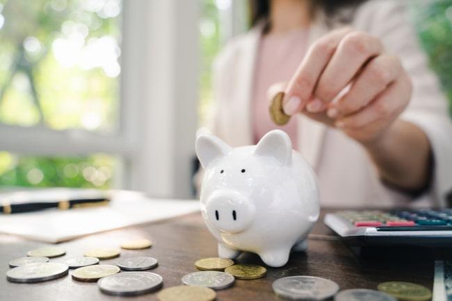 kvinna lägger ett mynt i spargris, vid skrivbord med mynt utspridda runt spargrisen