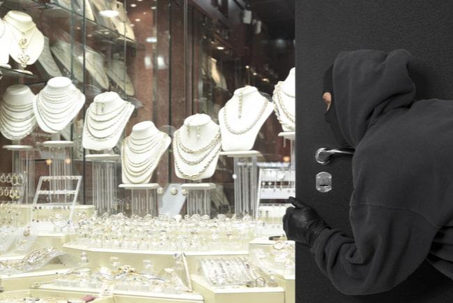 maskerad person gömmer sig bakom dörr och tittar på smycken i en butik