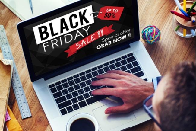 man vid laptop med black friday-annons på skärmen
