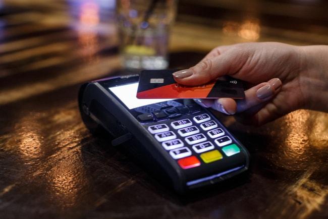 hand blippar ett betalkort vid betalterminal