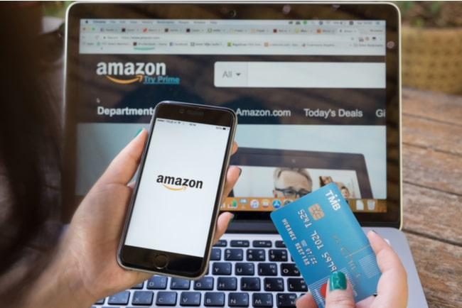 iphone med amazons logotyp och betalkort framför laptop med amazons hemsida på skärmen