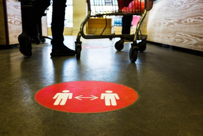 röd avståndsmarkering på golvet i butik