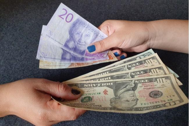 två händer växlar svenska sedlar och amerikanska sedlar