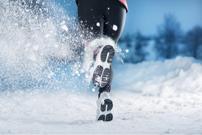 snö yr runt löparskor på person som springer