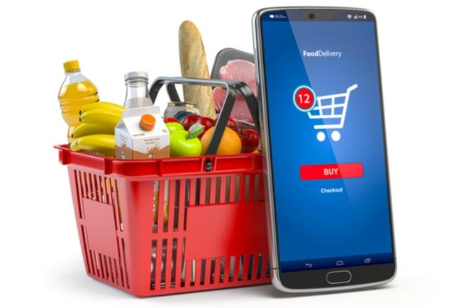 varukorg fylld med mat bredvid smartphone med beställning av matvaror uppe