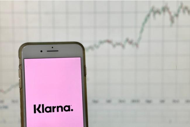 mobilskärm med klarnas logotyp framför ett diagram som visar en stark uppgång