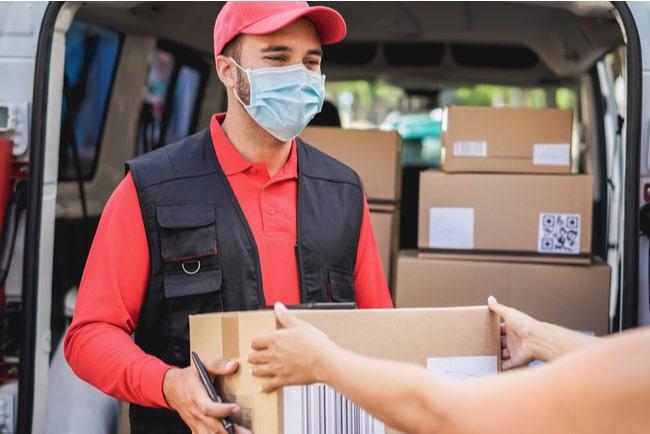 man med munskydd levererar paket i budbil