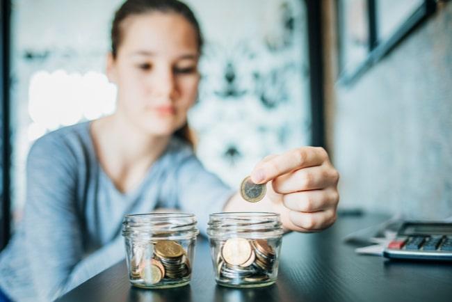 ung kvinna stoppar mynt i glasburkar