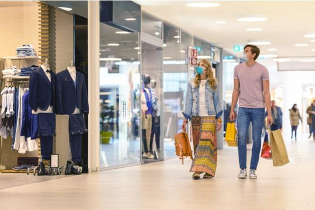par med munskydd bär på kassar i shoppingcenter