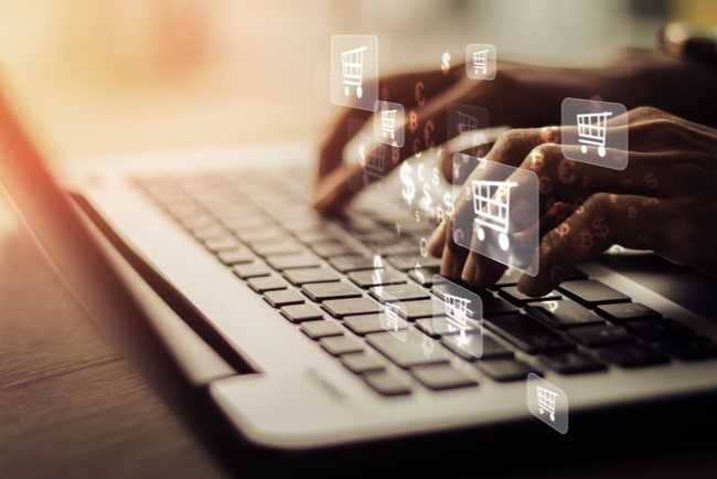 kundvagnsikoner och tecken för olika valutor flödar från tangentbord på laptop