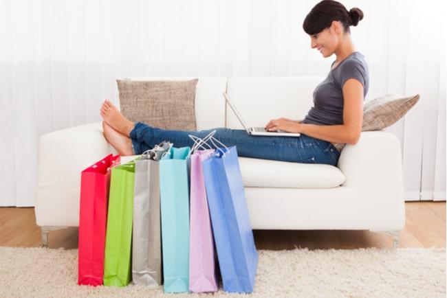 shoppingkassar framför glad kvinna med laptop i soffa