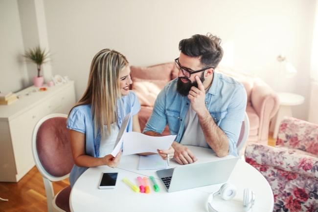 Kvinna och man ler mot varandra med ekonomipapper och dator framför sig.