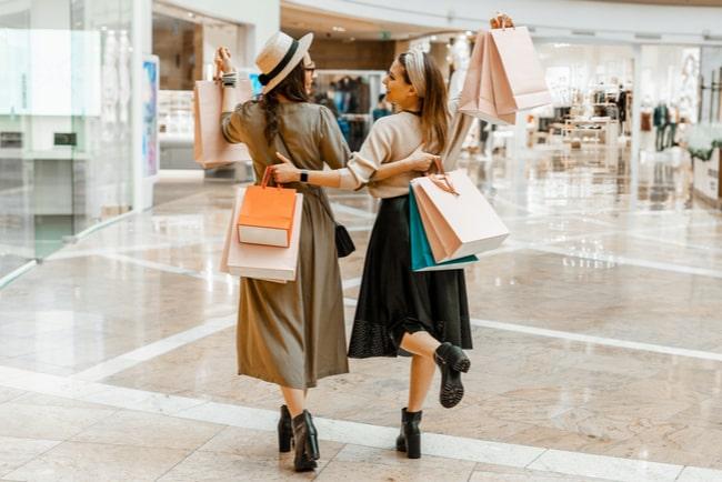 Två unga kvinnor i ett shoppingcentrum med shoppingkassar.
