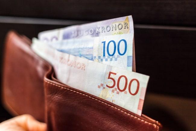 En brun plånbok med sedlar i olika valörer.