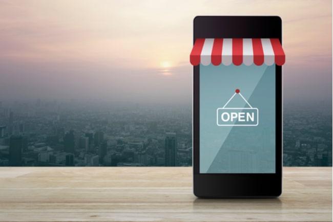 En smartphone står på träbord med en markis och en open-skylt på skärmen, e-handelskoncept.